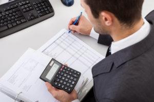 mężczyzna z kalkulatorem wyliczający zdolność