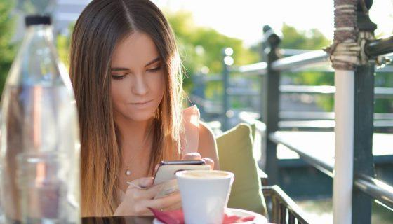Dziewczyna z telefonem przy kawie.